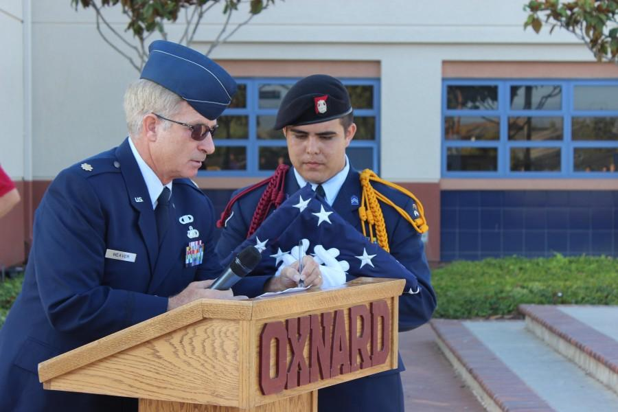OHS sophomore Andrew Felipe preparing the U.S. flag for the memorial service. Major Dale Weaver reviewing his speech prior to the event.