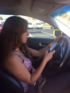 Oxnard High School senior Mary Allison Ihrke demonstrates texting and driving.