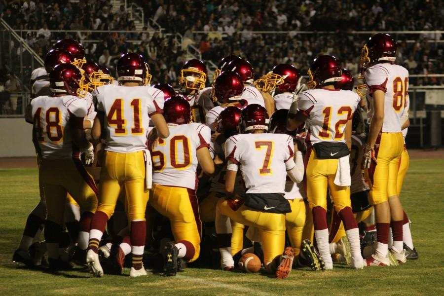 The+Oxnard+High+School+varsity+football+team+in+a+group+huddle+prior+to+their+game+against+the+Pacifica+High+School+Tritons.