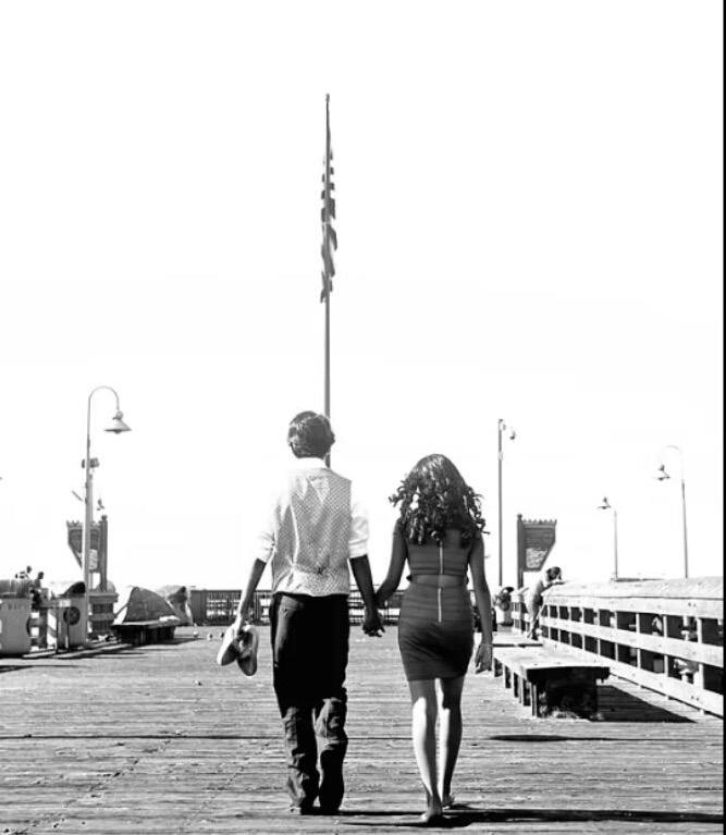 A couple takes a romantic walk on the Ventura Pier.